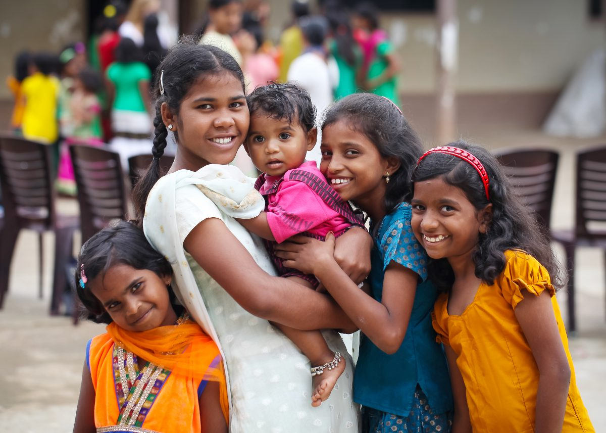 A group of smiling girls in bright cloths from the Children of Faith Home in India
