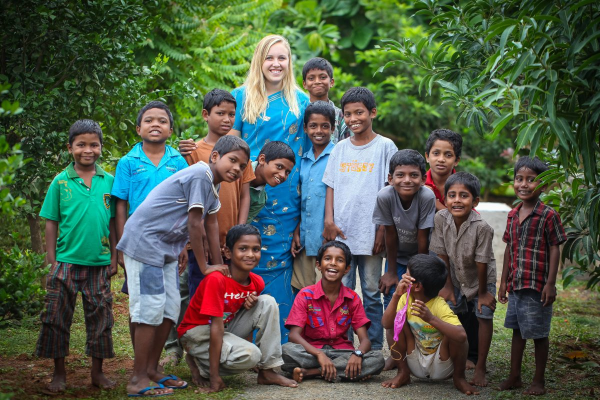 A volunteer from the United States poses with a group of boys from Children of Faith Home in India