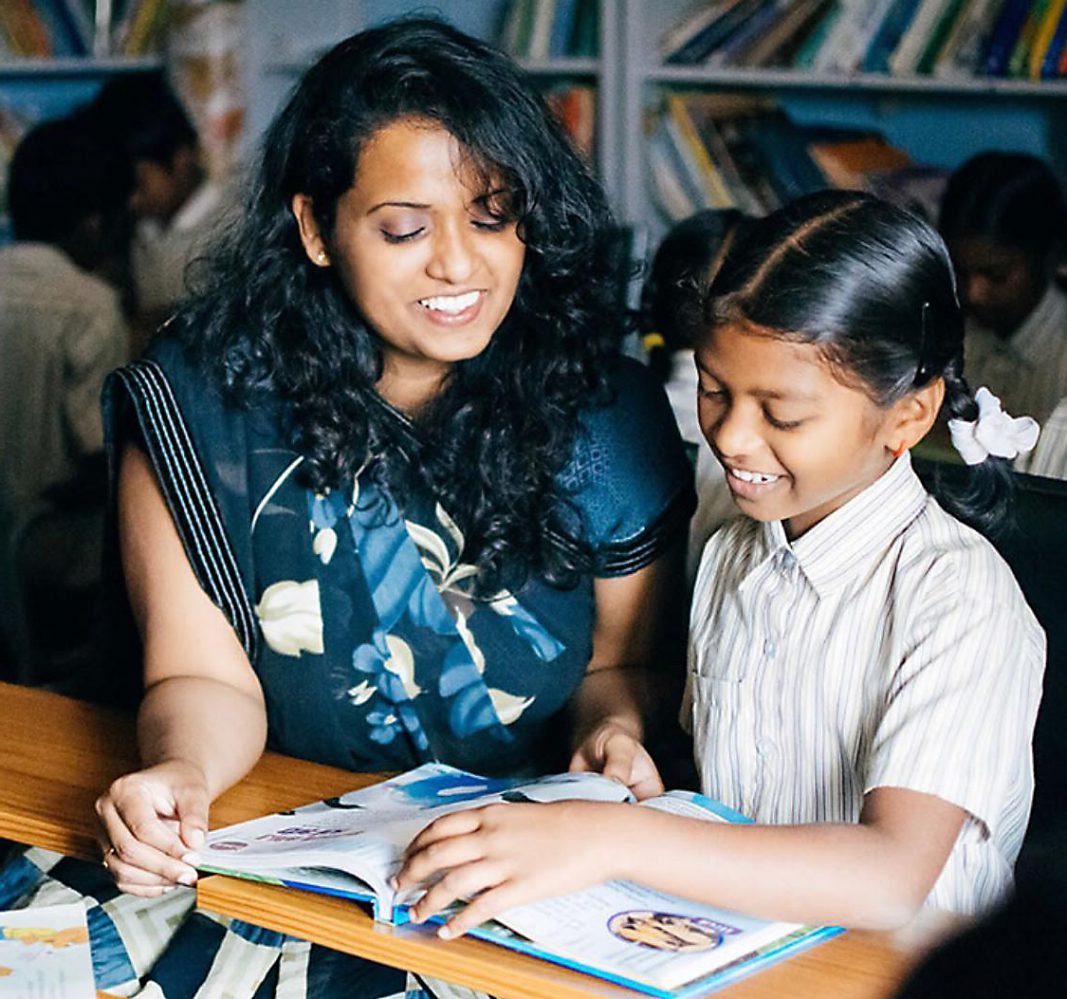 Rosie and young student reading over a workbook