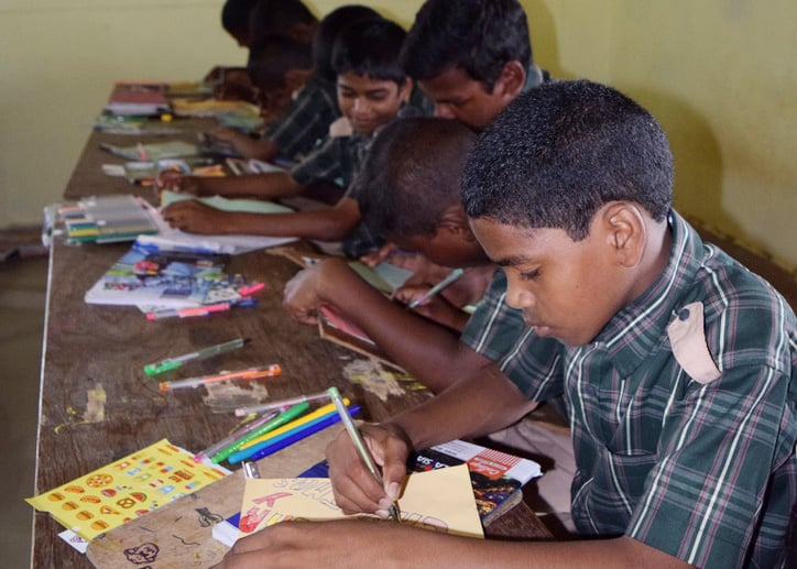 a boy at his classroom desk work on an assignment