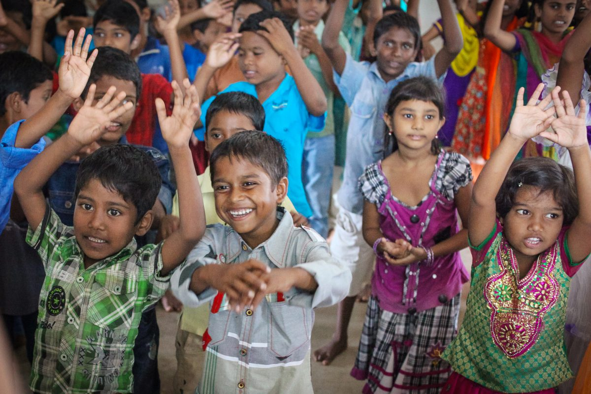 a group of young children at Children of Faith singing with hands in the air