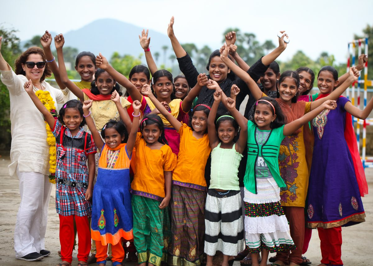 a group of young girls from Children of Faith with hands in the air with Rose and a visitor