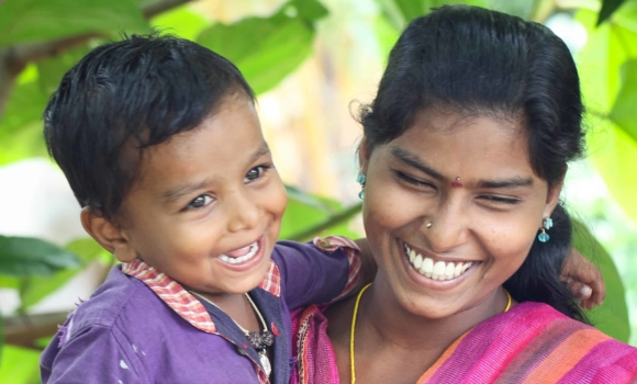 a young woman holding a young smiling boy on her hip