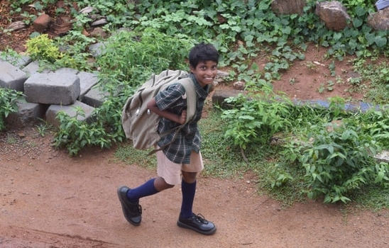 boy walking home with his backpack