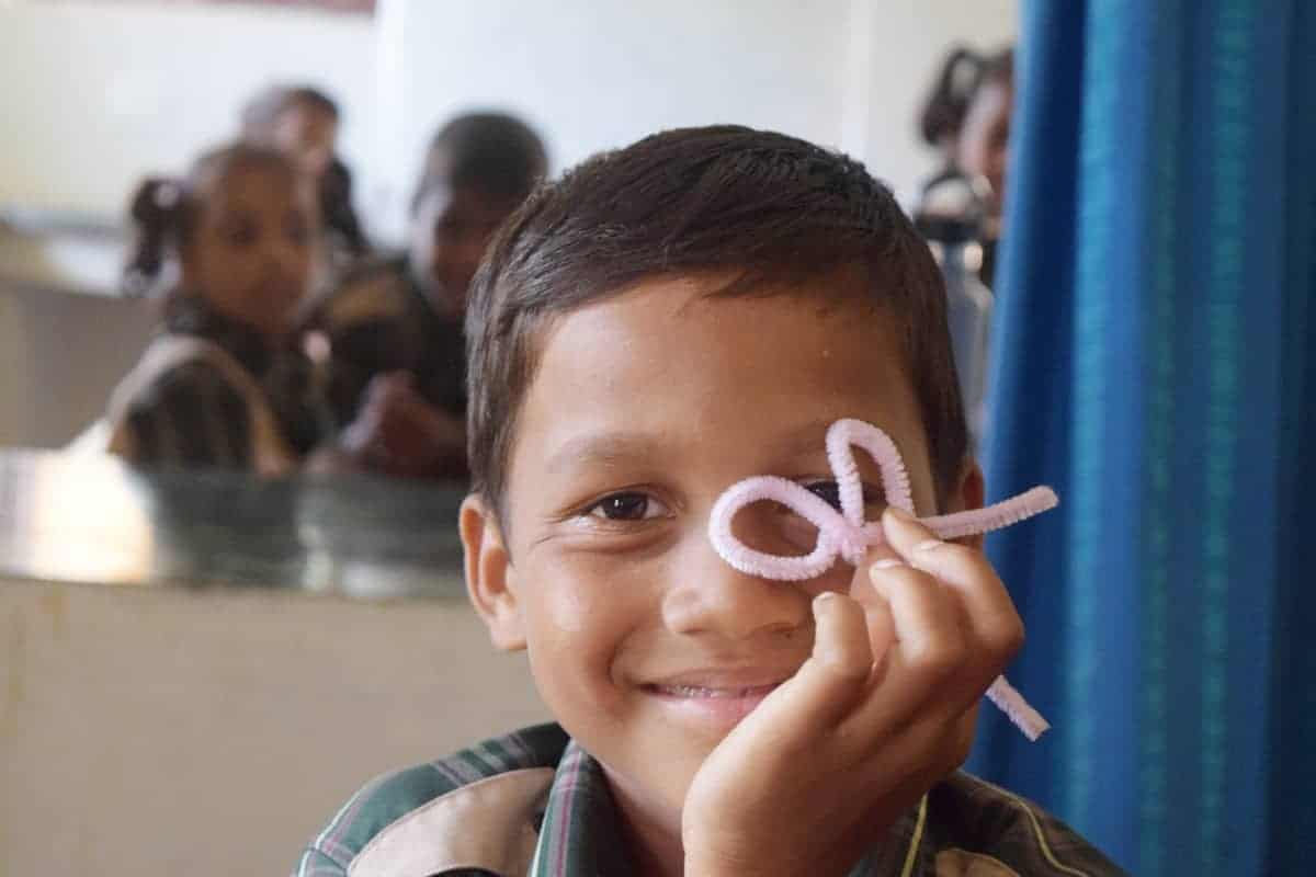 boy with pipecleaner project in classroom