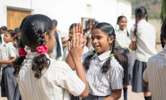 girls playing patty cake in school uniforms