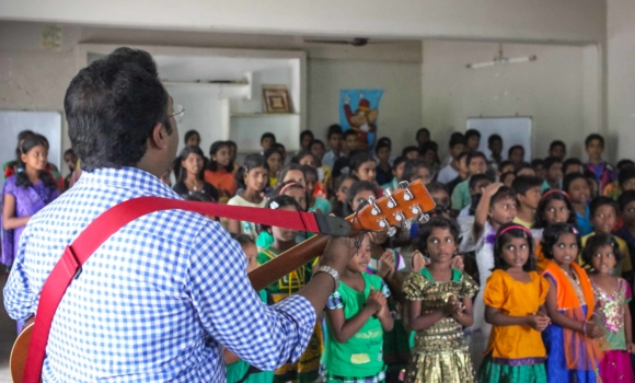 man with guiatr sining to group of children