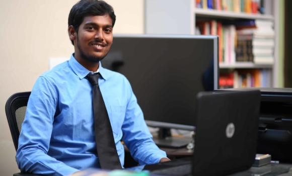 older student at computer desk
