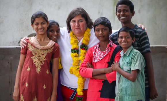 visitor to children of faith home with a group of kids