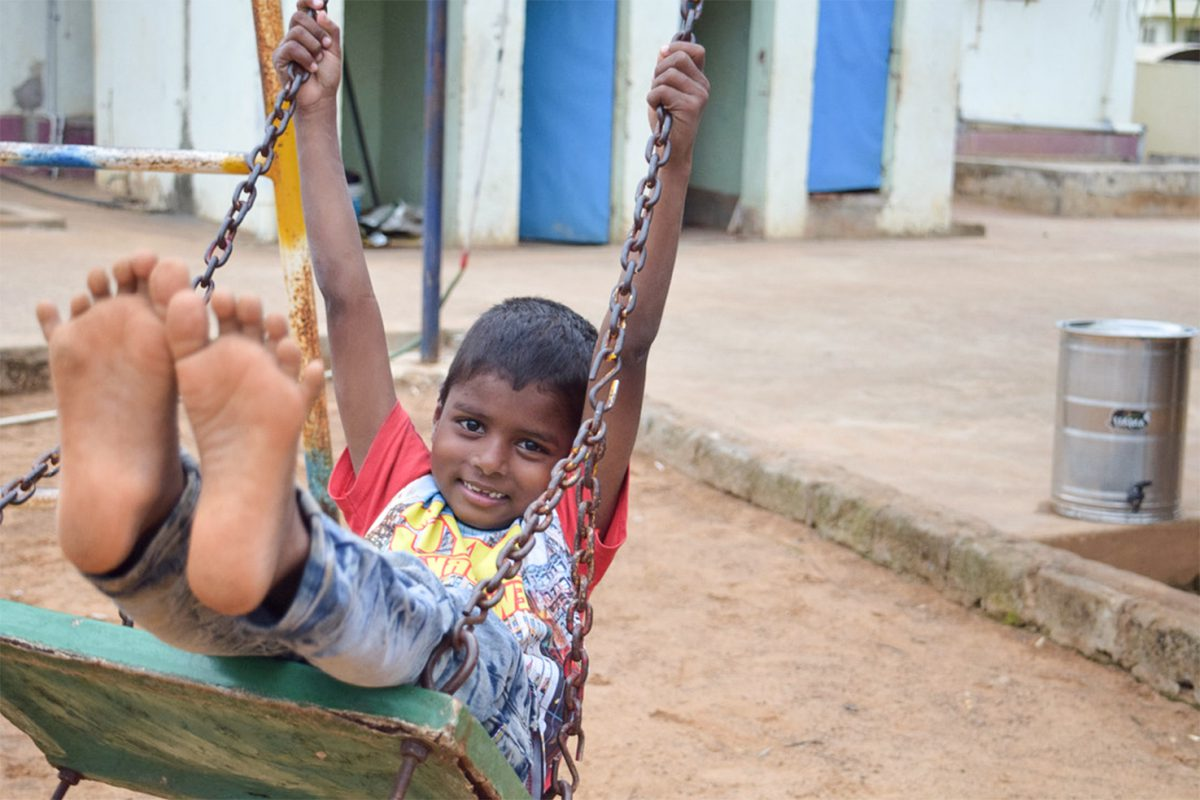 young boy playing on the swingset
