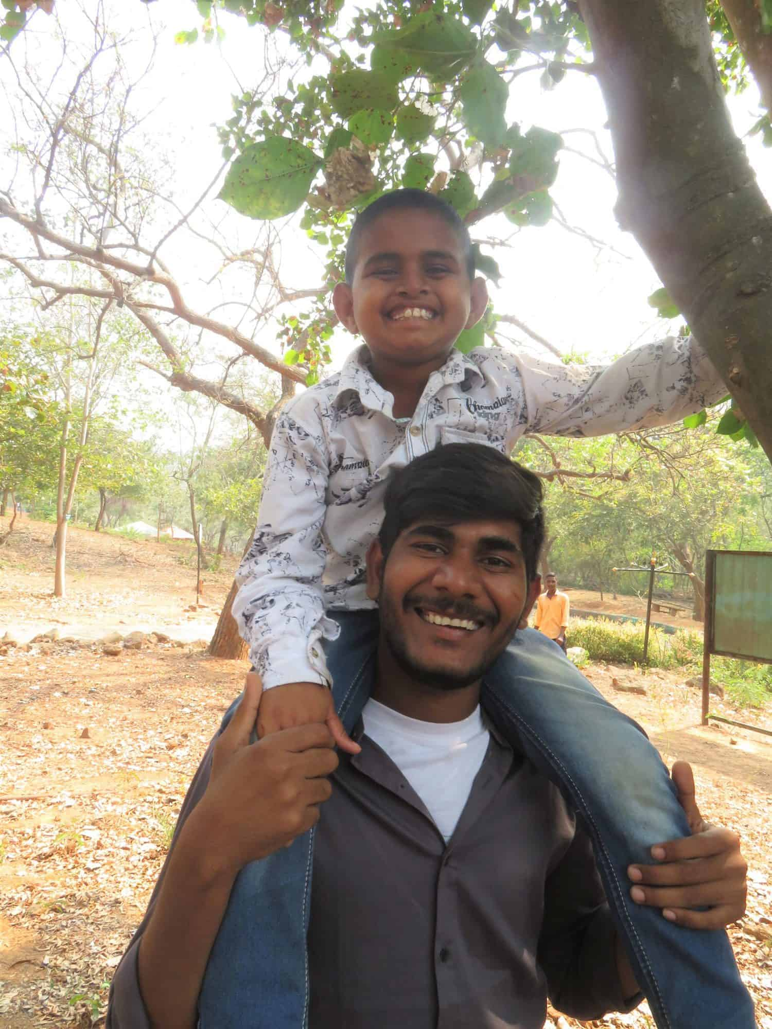 A young boy on the shoulders of a man outside in India