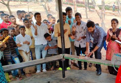 Children gather around their teacher to celebrate his birthday