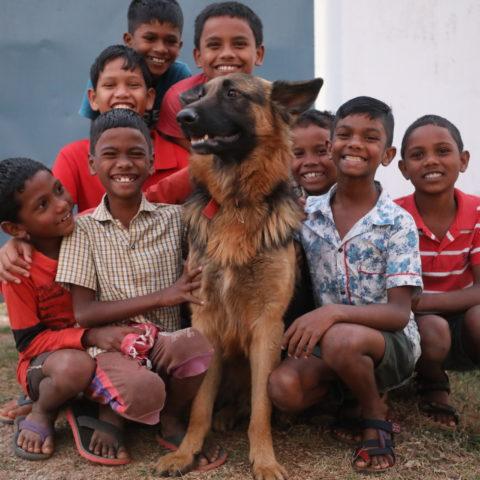 Boys surround their pet dog