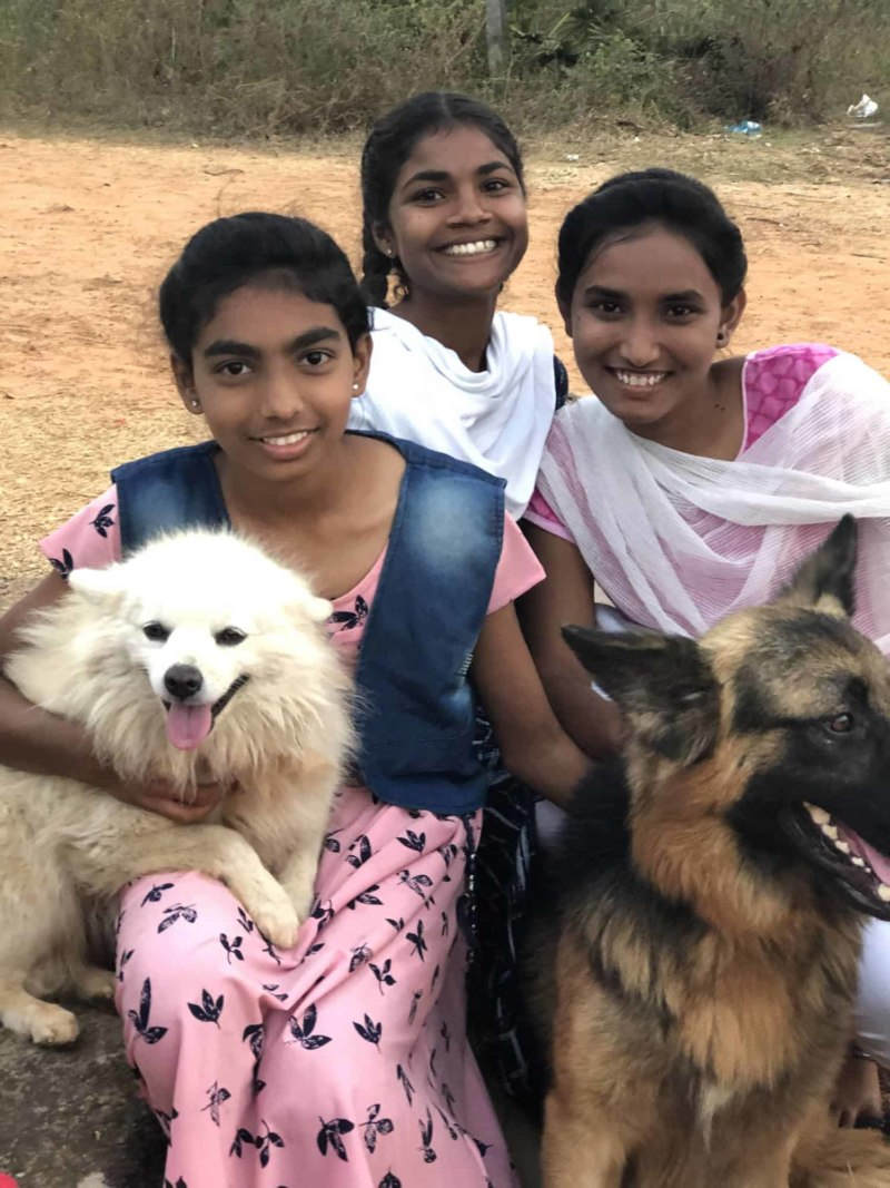 Three Indian girls hold two dogs
