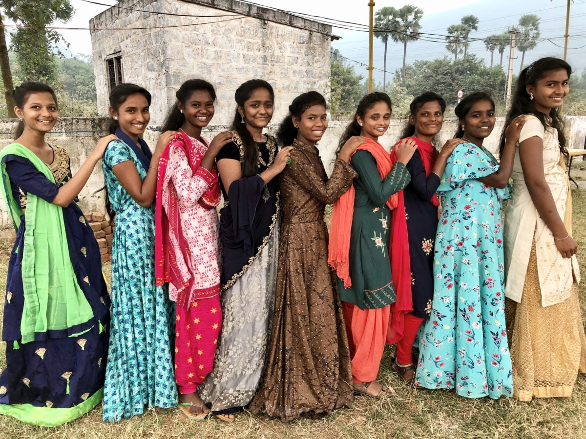 Girls in a line smiling at the camera in India