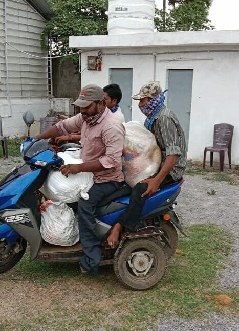Men on a motor bike transport supplies from Grocery distribution event in India
